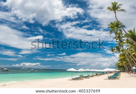 Tropical beach background from Alona Beach at Panglao Bohol island with Beach chairs on the white sand beach with cloudy blue sky and palm trees. Travel Vacation - stock photo