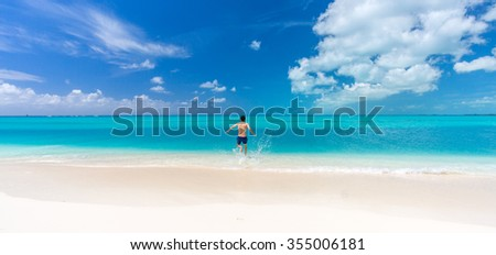 Tropical beach background with white sand beach and swimming man in Cayo Largo island. Cuba - stock photo