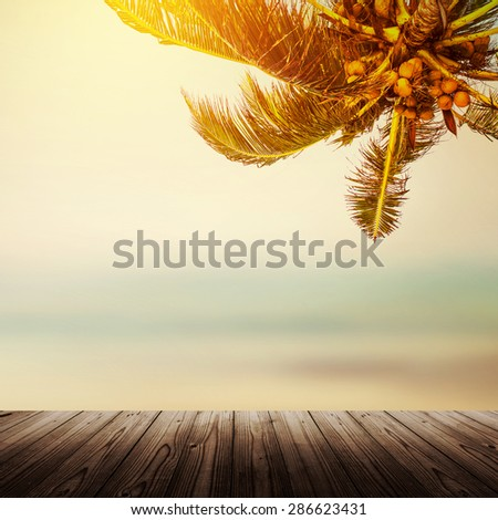 Tropical beach banner background. Coconut palm tree and blurry ocean. Empty wooden table. - stock photo