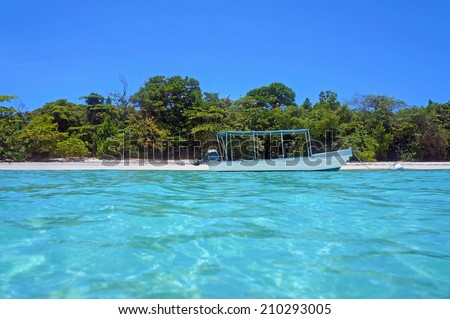 Tropical beach coastline with a boat, taken from water surface, Caribbean sea, Panama - stock photo