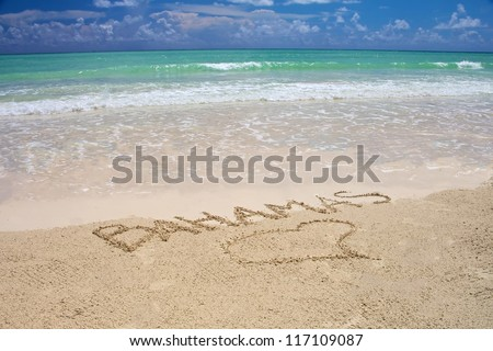 Tropical beach in Bahamas with bright blue sky, turquoise water and writing on the sand