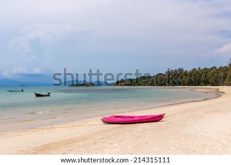 Tropical beach island with kayak - stock photo