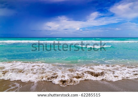 Tropical beach landscape with a dramatic cloudy sky - stock photo