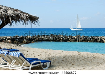 Tropical beach on St Maarten with sailboat - stock photo