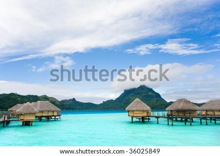 tropical beach over water bungalow vacation resort in bora bora tahiti - stock photo