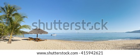 Tropical beach panorama with sunbeds, umbrellas, boats and palm tree - stock photo