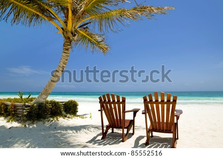 tropical beach, perfect place for relaxing, sun recliner in the shade of a palm tree. - stock photo