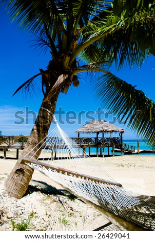Tropical beach, pier and hammock - stock photo
