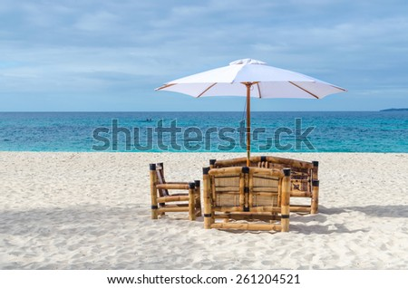 Tropical beach resort view with turquoise sea, lonely beach table with chairs from bamboo and umbrella on exotic white sandy Puka beach on Boracay, Philippines - stock photo