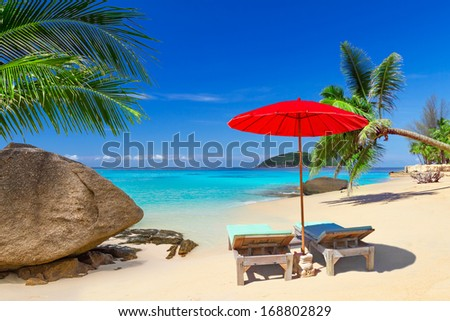 Tropical beach scenery with deck chairs in Thailand - stock photo