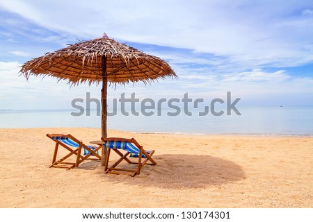 Tropical beach scenery with parasol and deck chairs in Thailand - stock photo