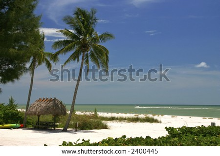 Tropical beach setting with a place to eat and a boat speeding by - stock photo