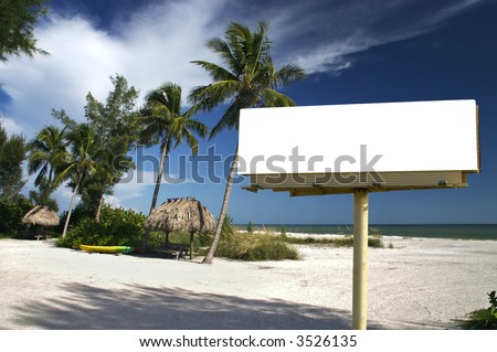 Tropical beach setting with a place to eat - included is a white billboard for you to place text or an advertisement - maybe for a travel ad? - stock photo