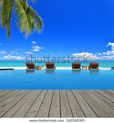 Tropical beach vacation and travel concept -- Boardwalk beside tropical beach resorts swimming pool - stock photo