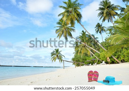 Tropical beach vacation and travel concept --  Sunhat with sunglasses and flip flops on tropical beach - stock photo