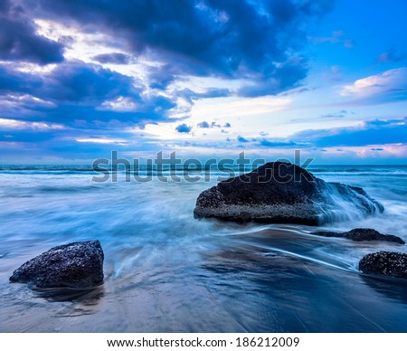 Tropical beach vacation background - waves and rocks on beach on sunset with beautiful cloudscape