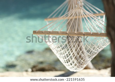 Tropical beach vacation concept with a hammock and turquoise water in the background - stock photo