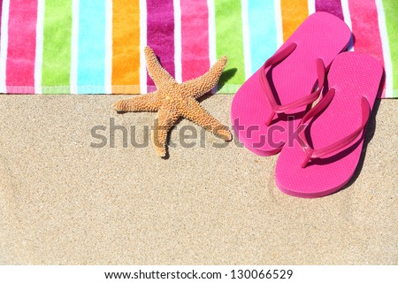 Tropical beach vacation holiday and travel concept with a colourful striped beach towel and vibrant pink sandal flip flip thongs on pristine sand with a starfish at an idyllic coastal beach resort. - stock photo