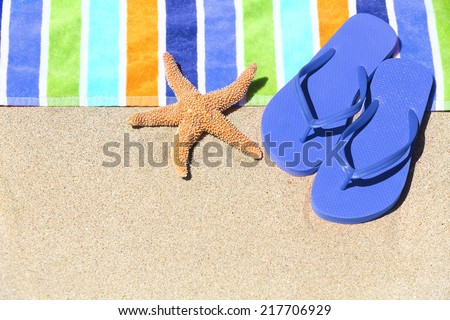 Tropical beach vacation holiday and travel concept with a colourful striped beach towel and vibrant blue sandal flip flip on pristine sand with a starfish at an idyllic coastal beach resort. - stock photo