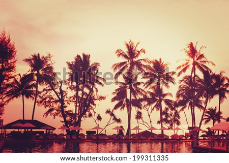 Tropical beach view. Palm tree and red sunset sky. Recreation area with sun umbrellas. - stock photo