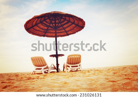 Tropical beach view. Two beach chairs with sun umbrellas. Vacation concept. Image toned in vintage warm colors. - stock photo
