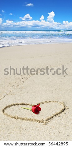 Tropical beach with a heart drawn and a red rose - stock photo