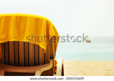 Tropical beach with beach chair and yellow towel. Holiday. - stock photo
