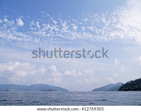 Tropical beach with clear blue water, blue sky and white cloud on a deserted coral island, Koh Adang south of Thailand. - stock photo