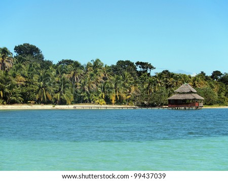 Tropical beach with coconut trees and a restaurant with thatched roof over water, Caribbean sea, Bocas del Toro, Panama - stock photo