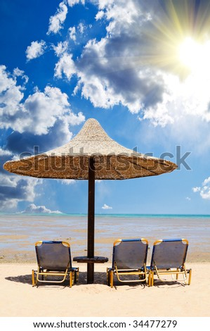 Tropical beach with empty loungers