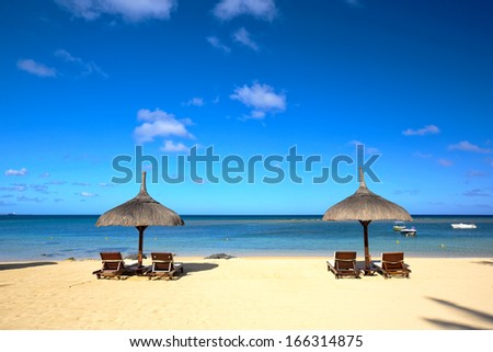 Tropical beach with lounge chairs and umbrella in Mauritius - stock photo