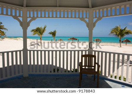 tropical beach with palm trees from white gazebo