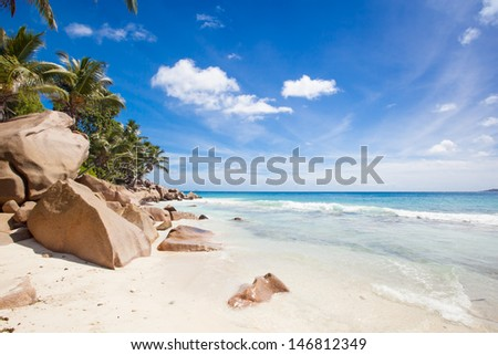 tropical beach with palm trees, granite rocks, a turquoise sea and a blue sky, La Digue, Seychelles - stock photo
