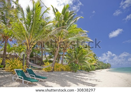 Tropical Beach with Palm Trees, Lounge Chairs and Palm-Thatched Huts - stock photo