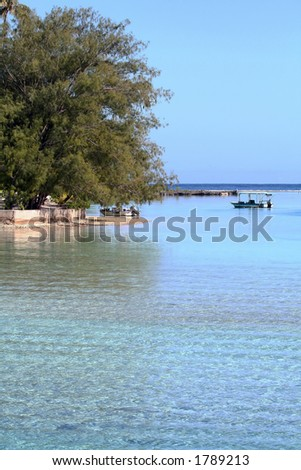 tropical beach with power boats at anchor - stock photo