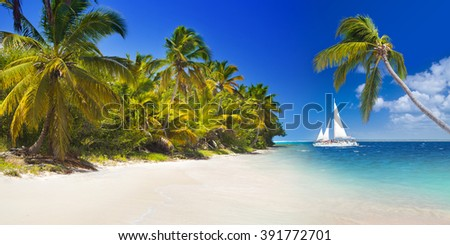 Tropical beach with sailing boat under the clear blue sky, Punta Cana, Dominican Republic