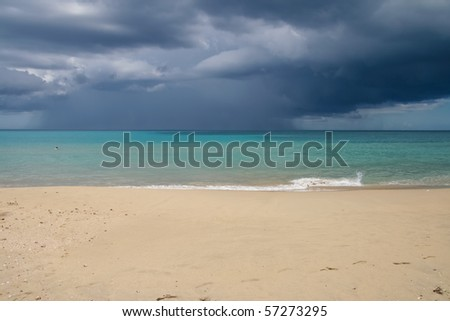 tropical beach with sea and an approaching stormy sky