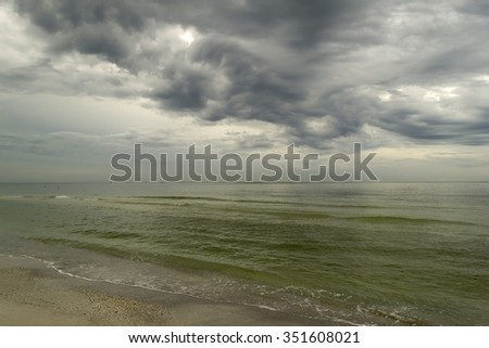 Tropical beach with shallow water and stormy dark sky - stock photo