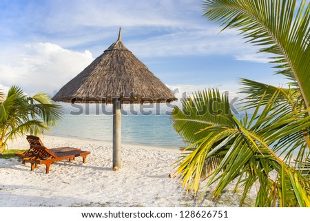 tropical beach with straw sunshade, palm leafs and a wooden sunbed - stock photo