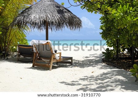 Tropical beach with sun chairs - stock photo