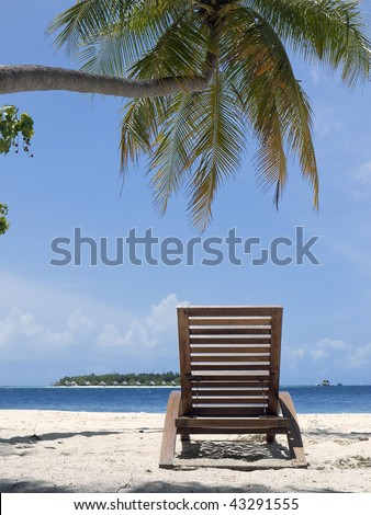 tropical beach with sun lounger under palm tree