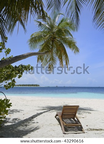 tropical beach with sun loungers under palm tree and view over ocean - stock photo