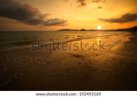 Tropical beach with sunset - stock photo