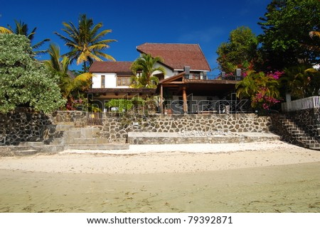 Tropical beach with villa on the shore of Mauritius island - stock photo