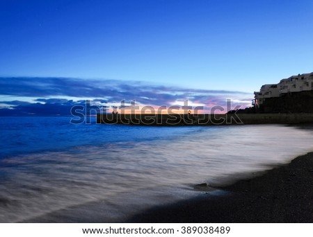 Tropical beach with volcanic sand after sunset time at Tenerife, Canary Islands, Spain  - stock photo