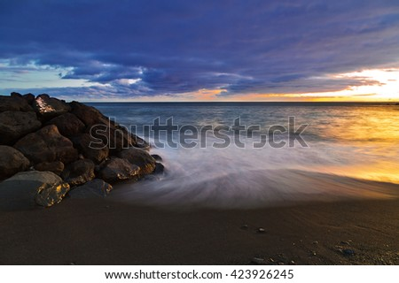 Tropical beach with volcanic sand in sunset time at Tenerife, Canary Islands, Spain  - stock photo