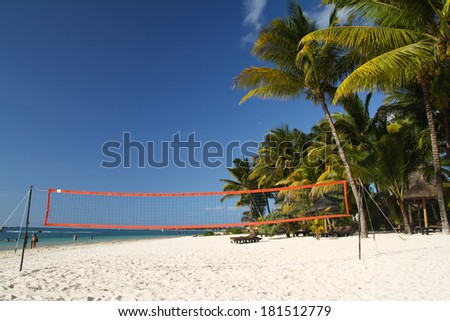 Tropical beach with volleyball net under palm trees, Mauritius - stock photo