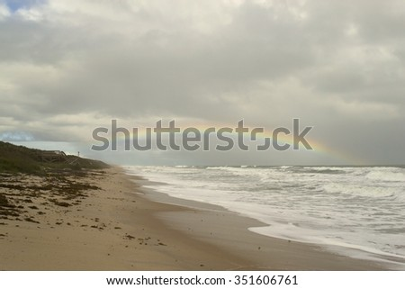 Tropical beach with waves breaking and rainbow in stormy dark sky - stock photo