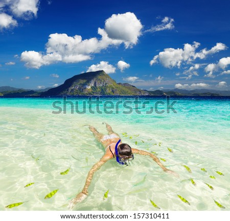 Tropical beach, woman swimming with snorkel - stock photo
