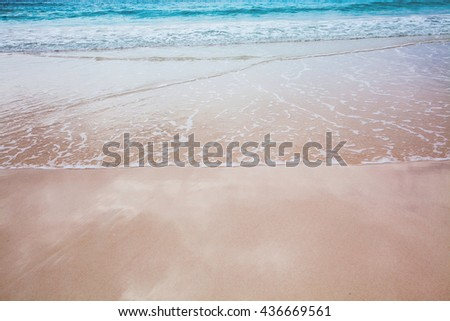 Tropical Bermuda beach with surf and reflections of the sky on the wet sand. - stock photo